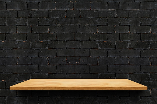 Leeres hölzernes brettregal am schwarzen backsteinmauerhintergrund für anzeigenprodukt