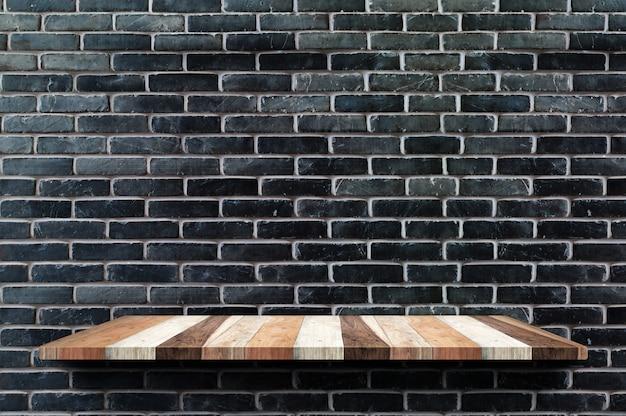 Leeres hölzernes brettregal am schwarzen backsteinmauerhintergrund