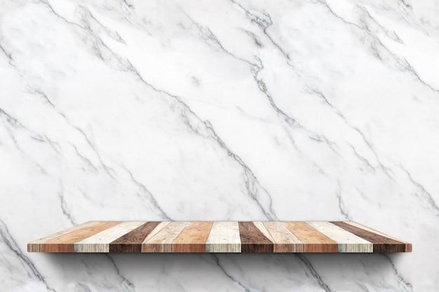 Leeres hölzernes plankenregal am weißen marmorwandhintergrund
