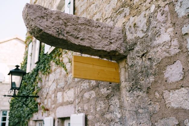 Leeres hölzernes schild auf einer steinnadel eines alten gebäudes