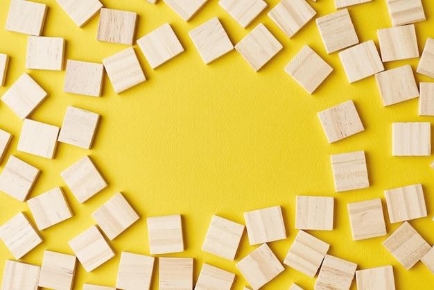 Leeres holzblockmuster auf gelbem hintergrund mit kopienraum, draufsicht