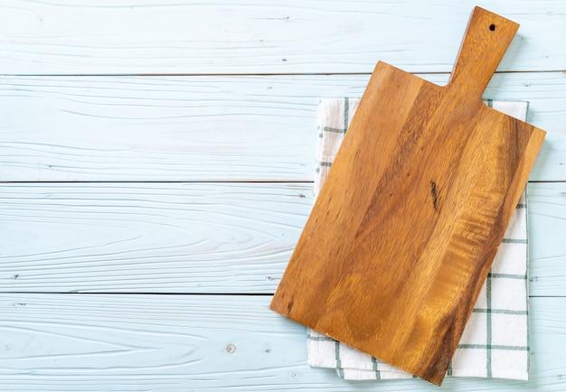 Leeres holzbrett mit küchentuch schneiden