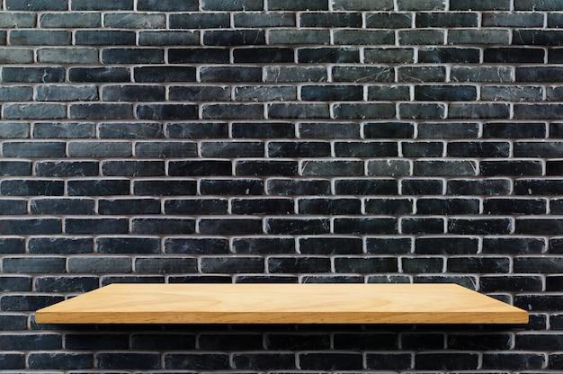 Leeres holzbrettregal am schwarzen backsteinmauerhintergrund