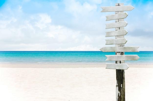 Leeres holzschild auf einem sandstrand und einem schönen seehintergrund im sommer.