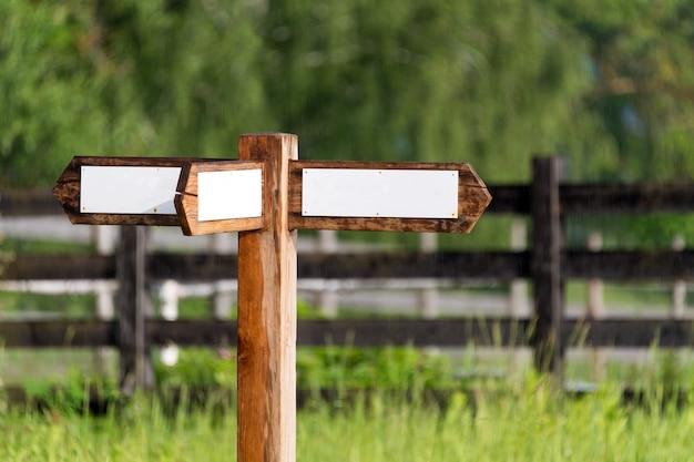 Leeres holzschild mit pfeilen auf der ranch. einfaches hölzernes straßenschild mit dreifachem richtungspfeil im garten mit holzzaun