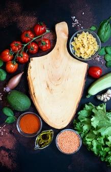 Leeres holzschneidebrett, umgeben von verschiedenem rohem gemüse, olivenöl, linsen, gewürzen, nudeln. veganes, vegetarisches essen, gesundes ernährungskonzept. rustikaler hintergrund, draufsicht, kopierraum