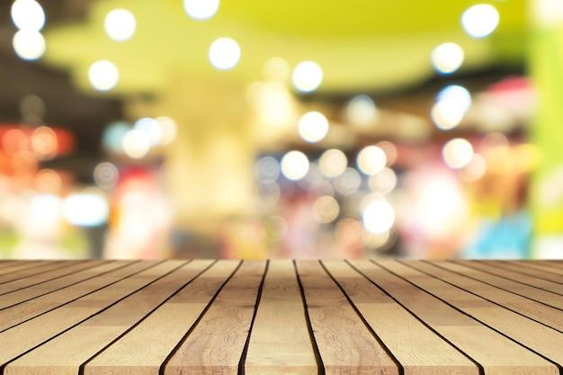 Leeres holztisch der perspektive über unscharfem einkaufszentrumhintergrund