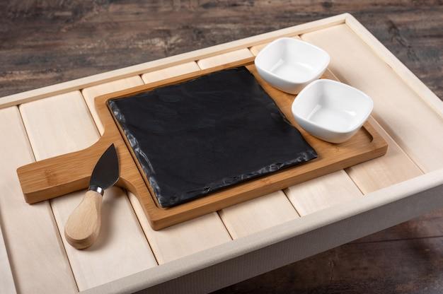 Leeres käse-servierbrett auf rustikalem holzhintergrund. leeres holztablett zum frühstück