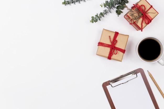 Leeres klemmbrett des arbeitsplatzes mit eukalyptus und geschenkbox auf weißem hintergrund