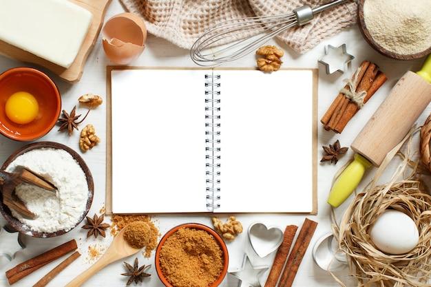 Leeres kochbuch, zutaten und utensilien zum backen von oben