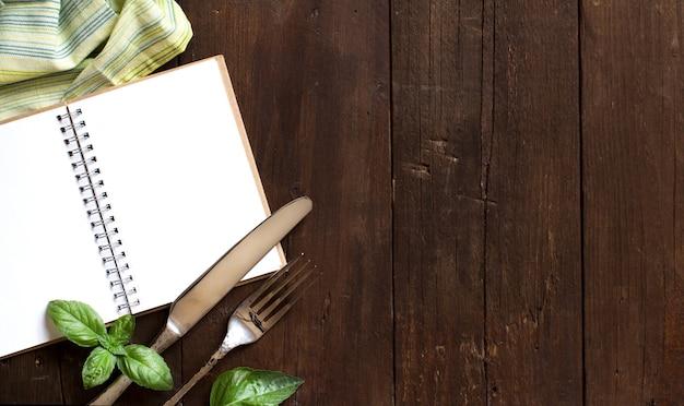 Leeres kochrezeptbuch mit gabel, messer, basilikum und serviette auf einem holztisch