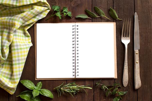 Leeres kochrezeptbuch mit gabel, messer, kräutern und serviette auf einem holztisch
