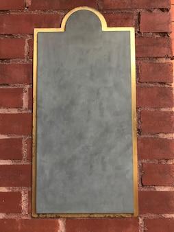 Leeres kreidebrettzeichen auf einer backsteinmauer