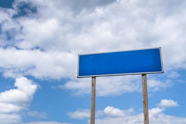Leeres landstraßenzeichen, zeiger auf einem hintergrund des blauen bewölkten himmels