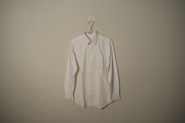 Leeres, langärmeliges weißes hemdmodell auf kleiderbügel an der vorderansicht des wandhintergrunds