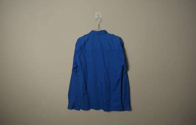 Leeres, langärmliges, blaues outdoor-hemdmodell auf einem kleiderbügel auf der rückseite der hintergrundwand