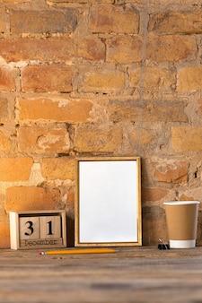 Leeres leeres bild oder blatt auf der braunen backsteinmauer mit kaffeetasse und bleistiften. 31. dezember, neujahrskonzept.