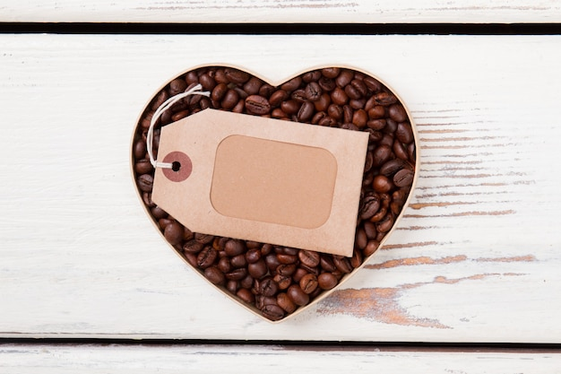 Leeres leeres etikett für exemplar, das über kaffeebohnen liegt. draufsicht flach. weißer hölzerner hintergrund.