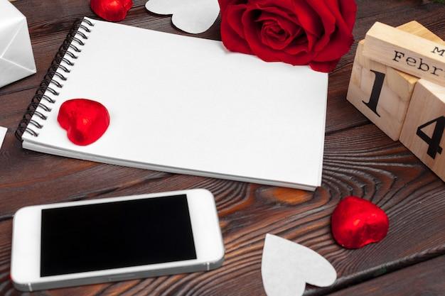 Leeres leeres notizbuch, geschenkbox, blumen auf einem weißen hintergrund, draufsicht