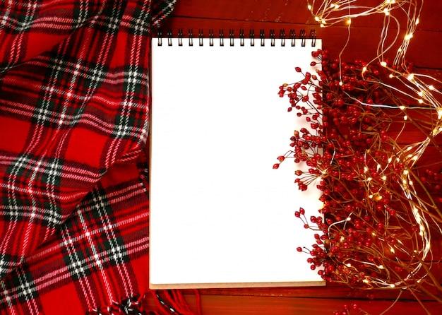 Leeres leeres notizbuch, niederlassungen mit roten beeren, rotem kariertem schal und glänzender girlande