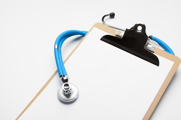 Leeres medizinisches klemmbrett mit stethoskop auf weißem hintergrund