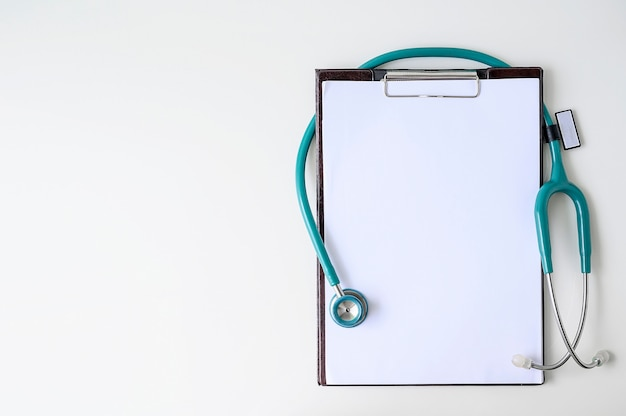 Leeres medizinisches klemmbrett mit stethoskop