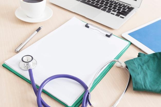 Leeres medizinisches klemmbrett und stethoskop auf hölzernem schreibtisch