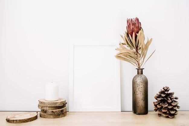 Leeres modell eines bilderrahmens mit protea-blume und trendigem zeug auf weißem hintergrund