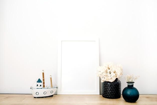 Leeres modell eines bilderrahmens mit trendigen sachen auf weißem hintergrund
