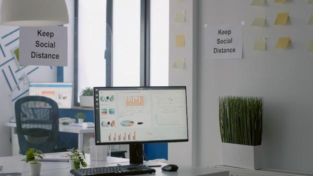 Leeres modernes büro mit kunststofftrennern und schild mit sozialer distanz an der wand. moderner arbeitsplatz im unternehmen während der covid-19-coronavirus-pandemie