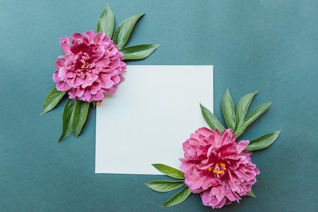 Leeres notizblockblatt und burgunderfarbene pfingstrosen flach auf blauem hintergrund. sommerkonzept mit platz für text, modellock
