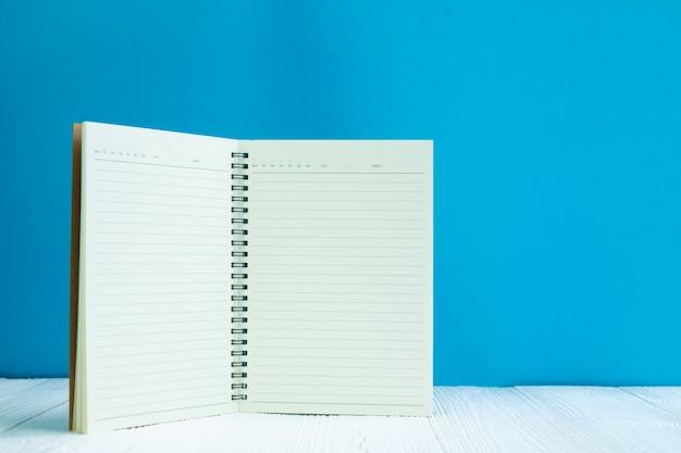 Leeres notizbuch auf blauem wandhintergrund der weißen hölzernen tabellenfront mit kopienraum für addieren text oder werbungswort.