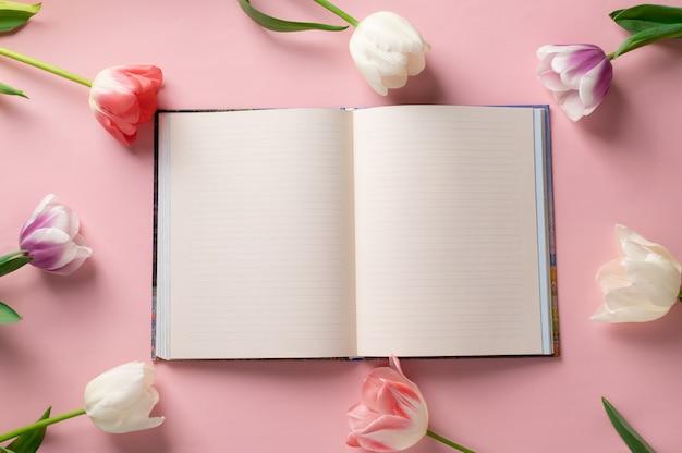Leeres notizbuch auf einem rosa hintergrund mit einem rahmen der schönen blumen. hobelkonzept. platz für text. flach liegen, draufsicht
