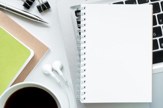 Leeres notizbuch auf moderne weiße schreibtischtabelle. draufsicht, flach zu legen.