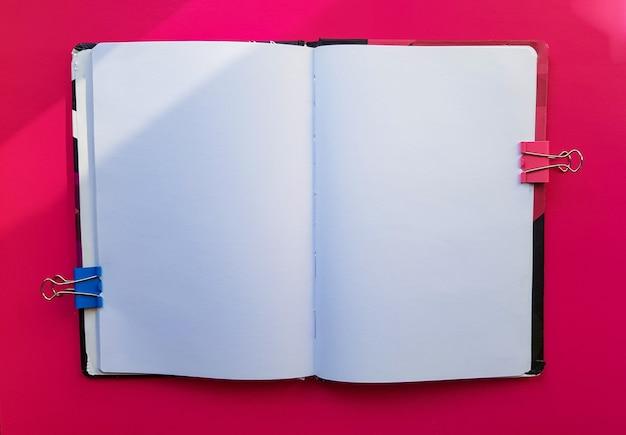 Leeres notizbuch auf rotem grund. leere seiten eines offenen buches, platz zum schreiben und text. von oben betrachten. platz kopieren, flach legen.