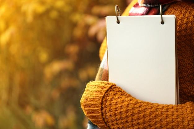 Leeres notizbuch in den händen auf dem herbst, der im sonnenuntergang verwischt wird, rays hintergrund