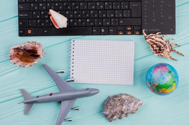 Leeres notizbuch in reisender zusammensetzung. flugzeug, globus, muscheln auf blauem schreibtisch.