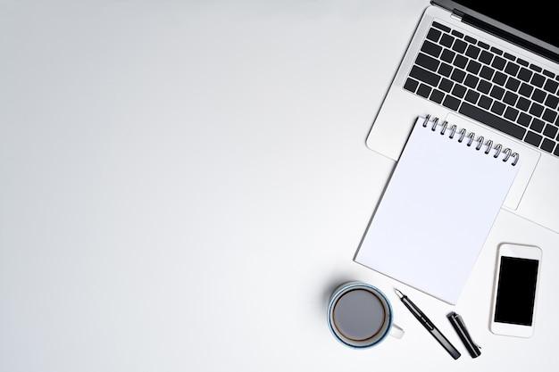 Leeres notizbuch, laptop-computer und smartphone auf weißem schreibtisch.