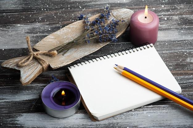 Leeres notizbuch, lila aromakerzen und trockene lavendelblumen auf rustikalem holztisch.
