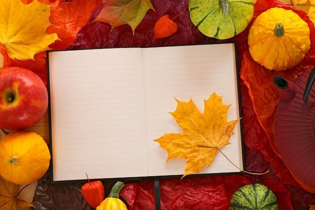 Leeres notizbuch mit ahornblatt, äpfeln und kürbisen