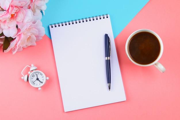 Leeres notizbuch mit blauem stift auf einem rosa pastellhintergrund. modell, rahmen, vorlage