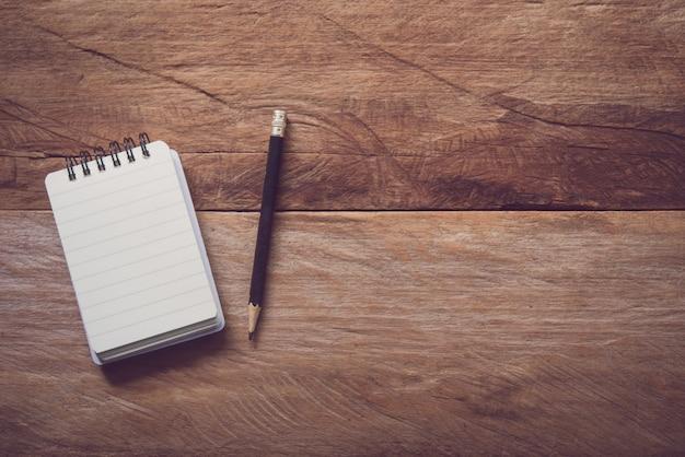 Leeres notizbuch mit bleistift auf holztisch