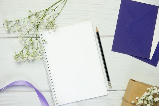 Leeres notizbuch mit bleistift auf weißem hölzernem hintergrund. flache komposition mit freiem platz für text.
