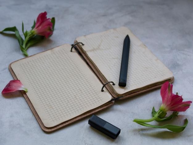 Leeres notizbuch mit blume auf grauem hintergrund