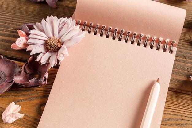 Leeres notizbuch mit blume auf weinleseholztisch