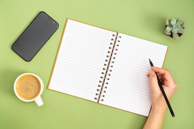 Leeres notizbuch mit der leeren seite, kaffeetasse und hand, die einen bleistift halten. tischplatte, arbeitsplatz auf grünem hintergrund. kreative flachlage.