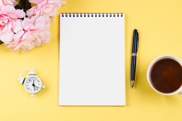 Leeres notizbuch mit einem blauen stift auf einem gelben pastellhintergrund. modell, rahmen, vorlage.