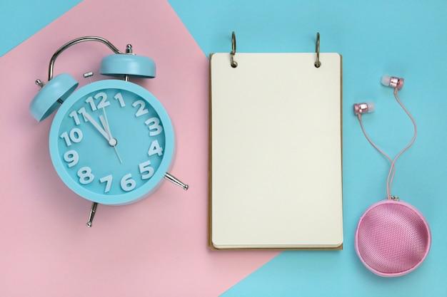Leeres notizbuch mit einem blauen wecker auf einem kombinierten hintergrund