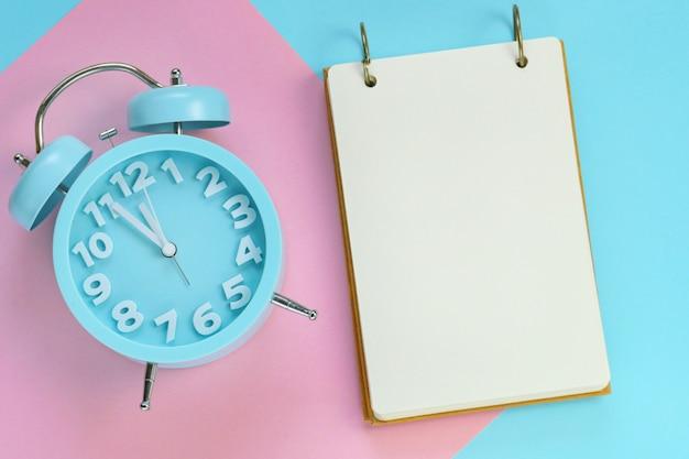 Leeres notizbuch mit einem blauen wecker auf einem papier kombinierte hintergrund