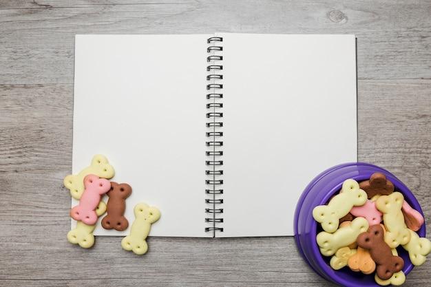 Leeres notizbuch mit hundenapf mit lebensmittel